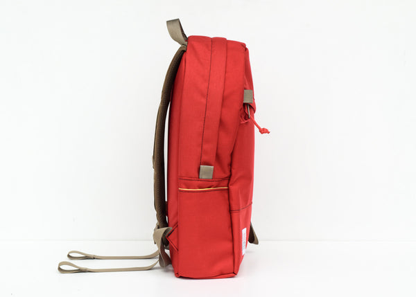 The Topo Designs Daypack in red from the side.