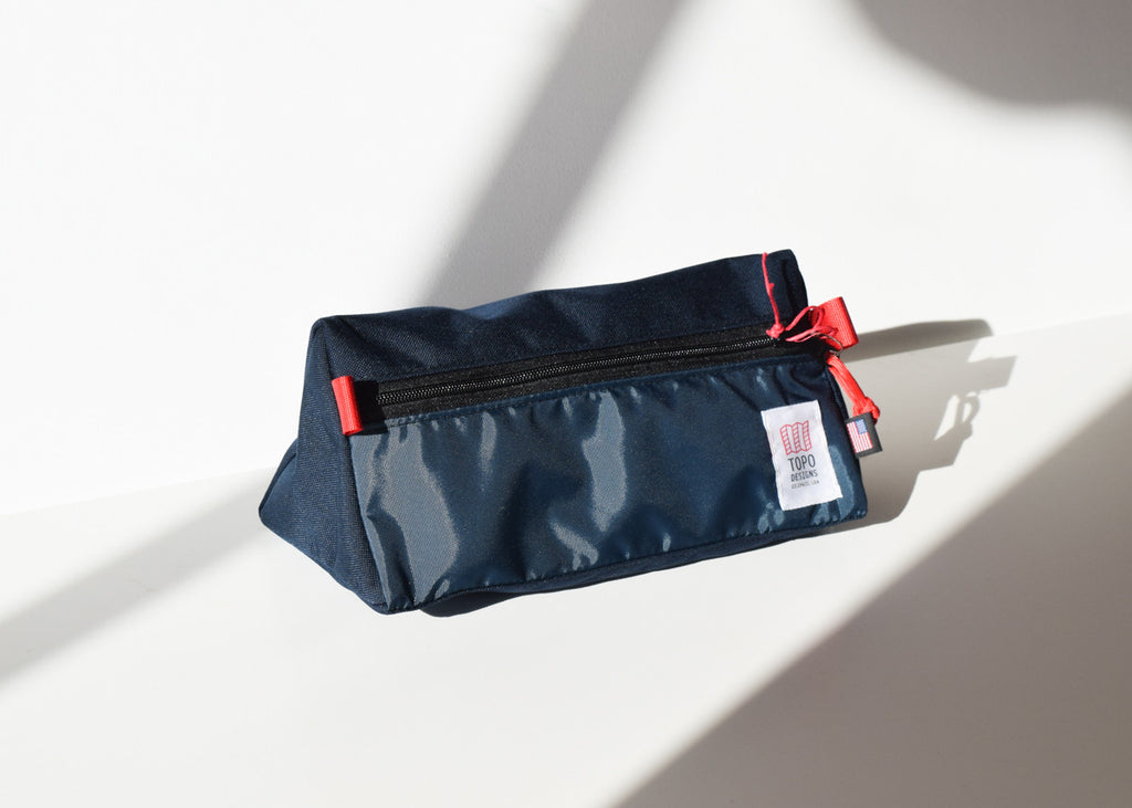The Topo Designs Dopp Kit in navy in the sun.