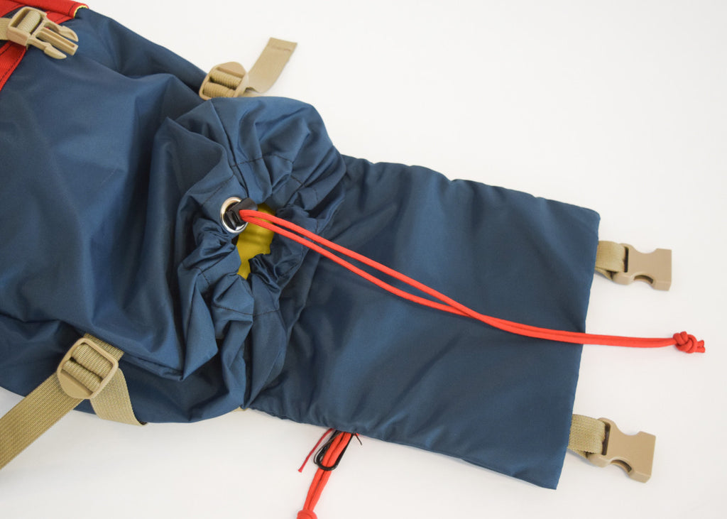 Topo Designs Rover Pack in navy/red with drawstring closure.