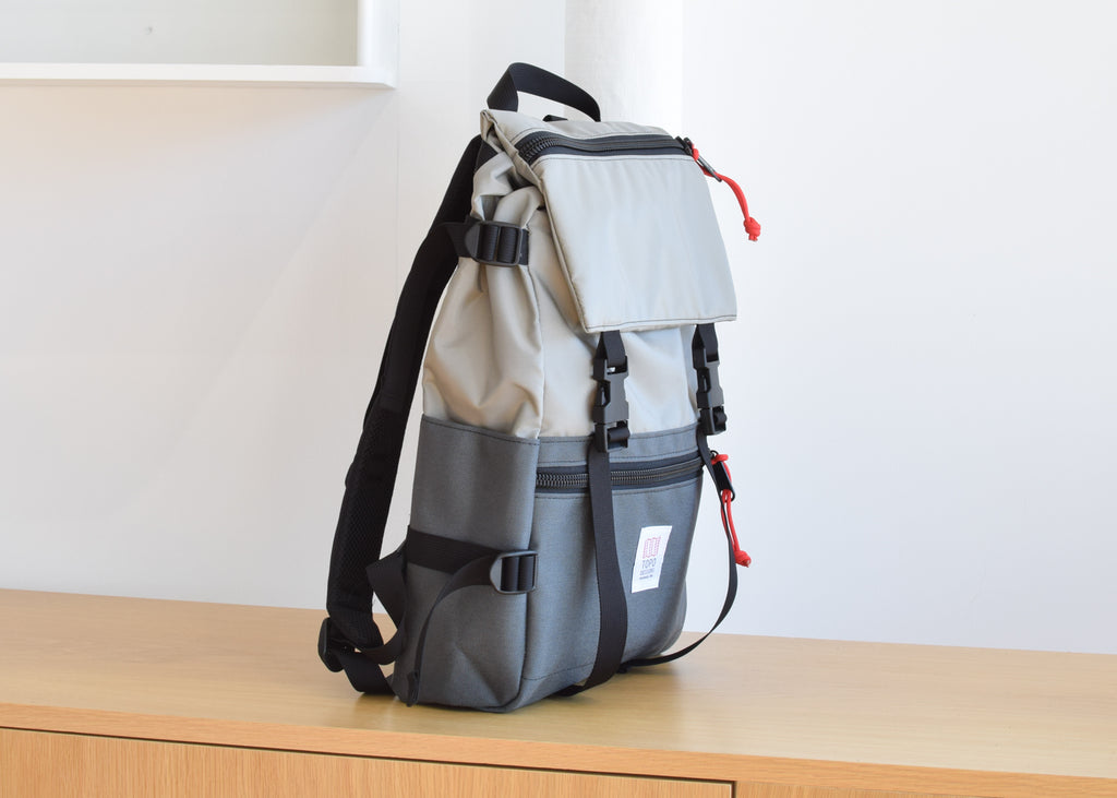 The Topo Designs Rover Pack in Silver/Charcoal from the side with backpack straps.