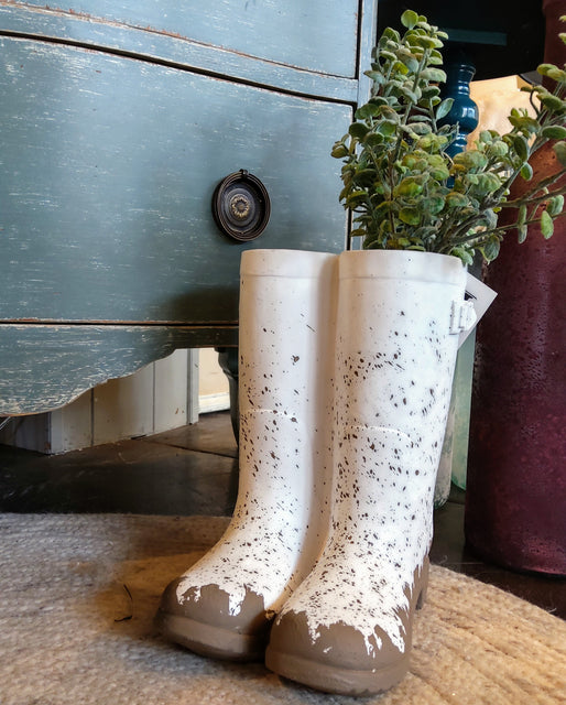 """Muddy"" ceramic rainboots that act as a planter, featuring a small faux plant inside"