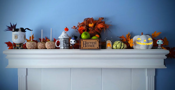 Fireplace mantle featuring Halloween decorations such as monsters, skeletons, fall garland, and a jack-o-lantern