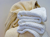 A pair of Bethel cotton blankets stacked on a chair, showing the color variations, Natural and White.