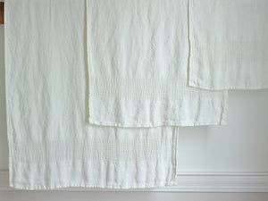 Bradbury bath sheet, bath towel and hand towel hanged on a rack next to each other, all in Pearl color variation.