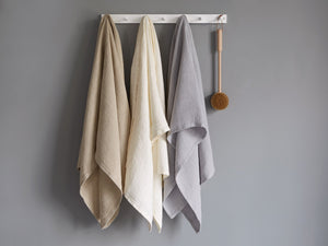 Three different Calendar Island towels hanged by a wooden rack.