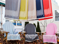 Fez Wool Throws showcased in a garden, presenting all the color variations.