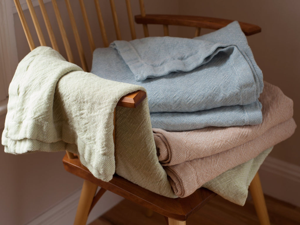Stack of Lamoine linen blankets on a chair.