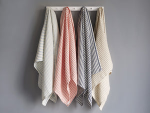 McClary towels in different colors hanged on a wall rack.