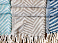 Three Monhegan throws next to each other in different colors.