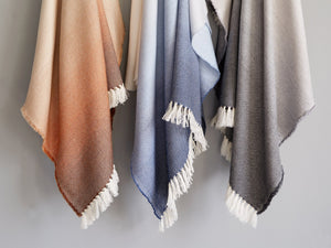 Three different Palermo wool throws hanged on a wall rack.