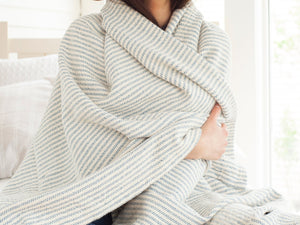 Woman covering herself in a Winslow blanket.