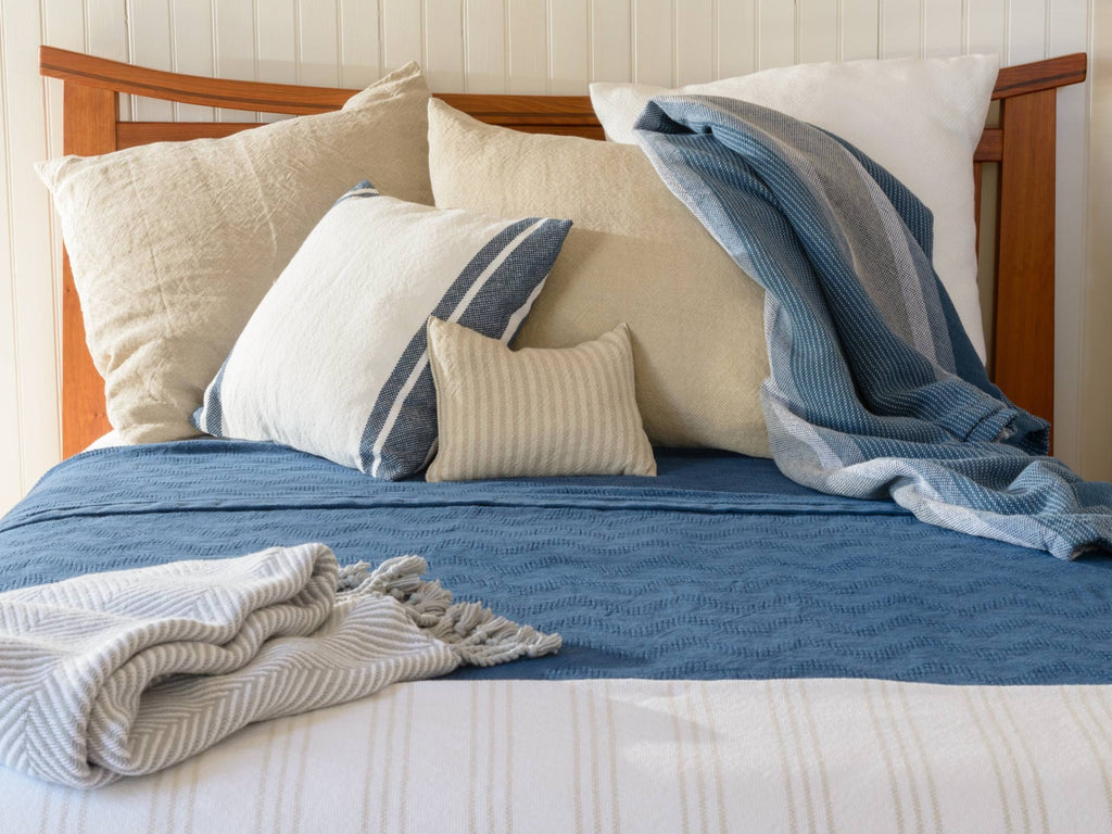 Blue Heron and Monhegan throws showcased on a bed.