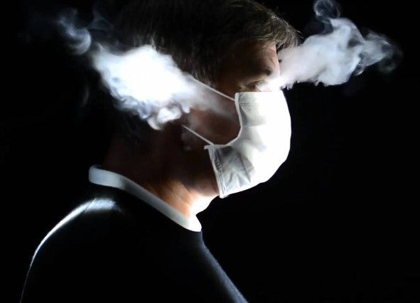 a man wearing face mask and aerosols coming out from his mask