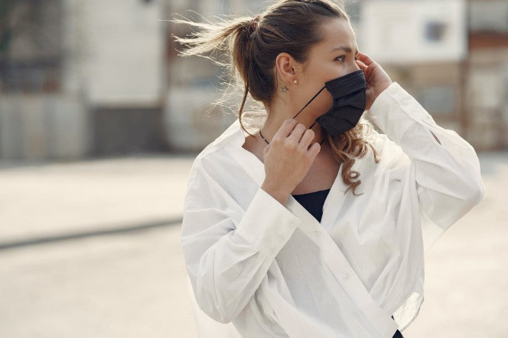 woman wearing white shirt putting a mask