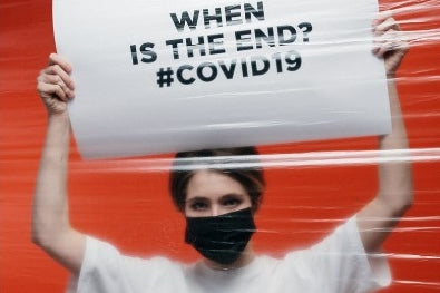 a woman holding a sign and wearing face mask
