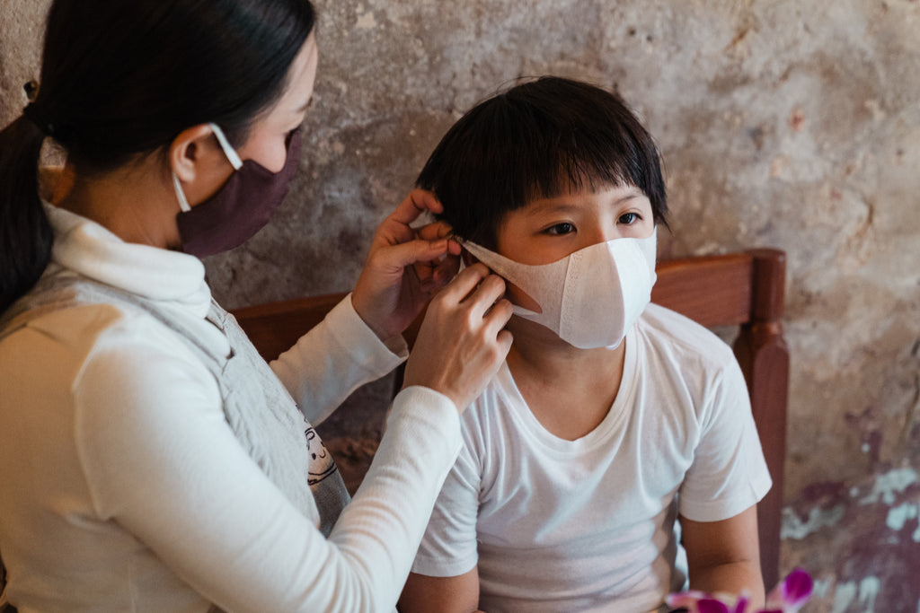 a woman putting mask on his son