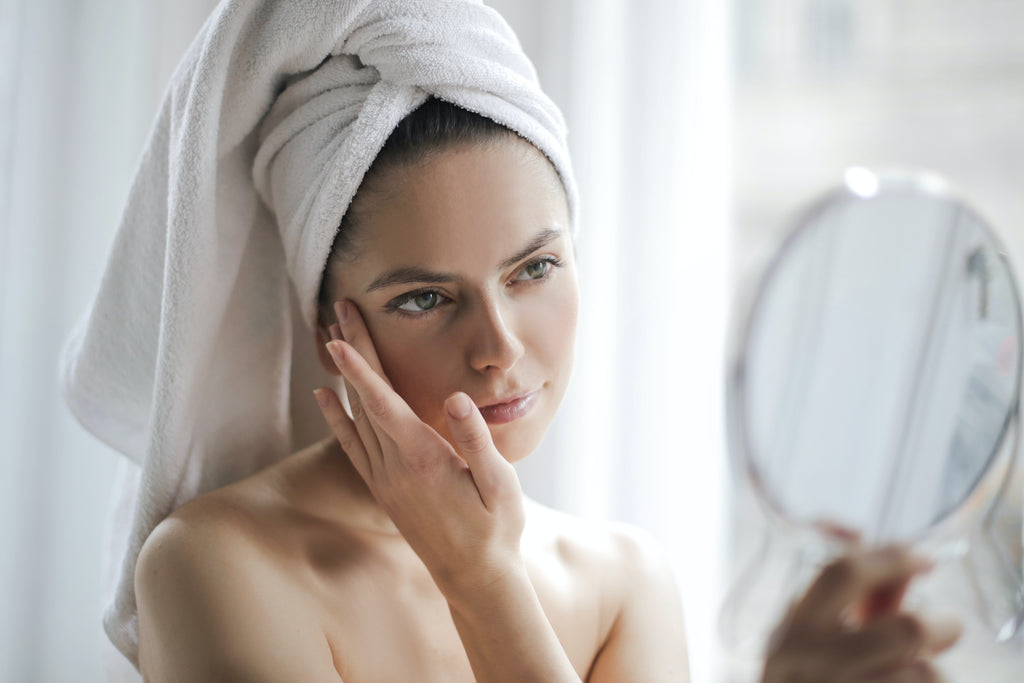 A woman touching her face while looking at the mirror