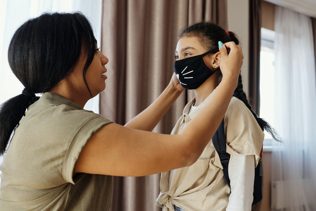 A woman putting face mask on her child