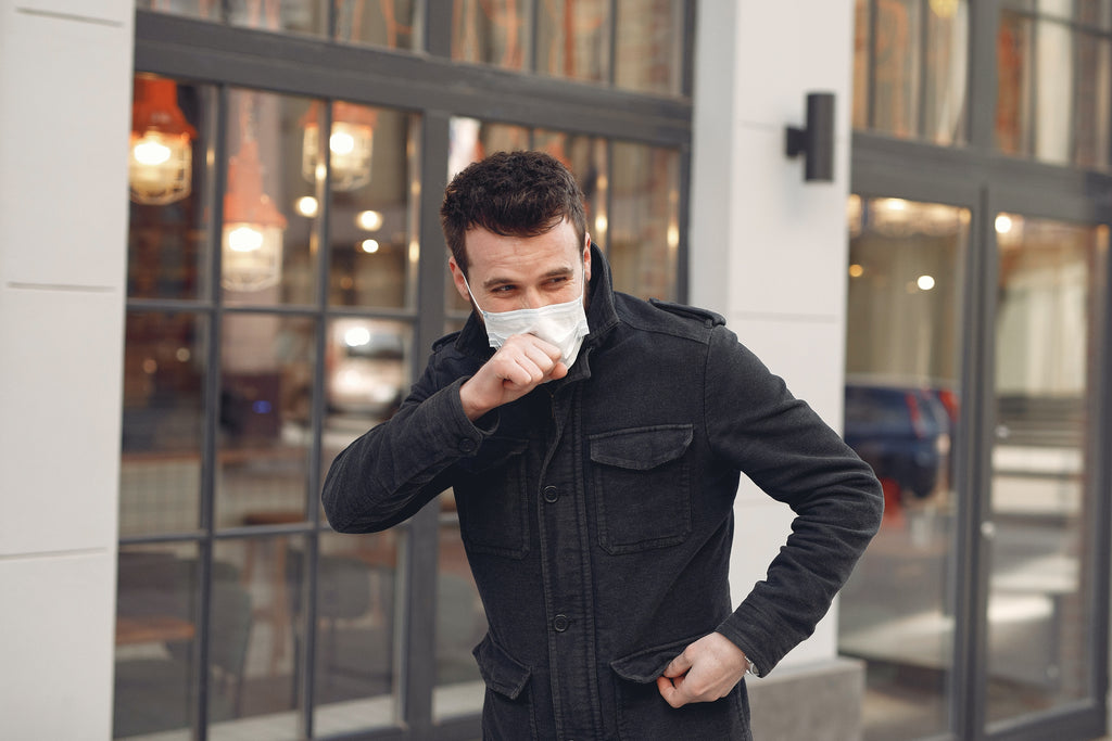 a man wearing black jacket and facemask coughing on the street