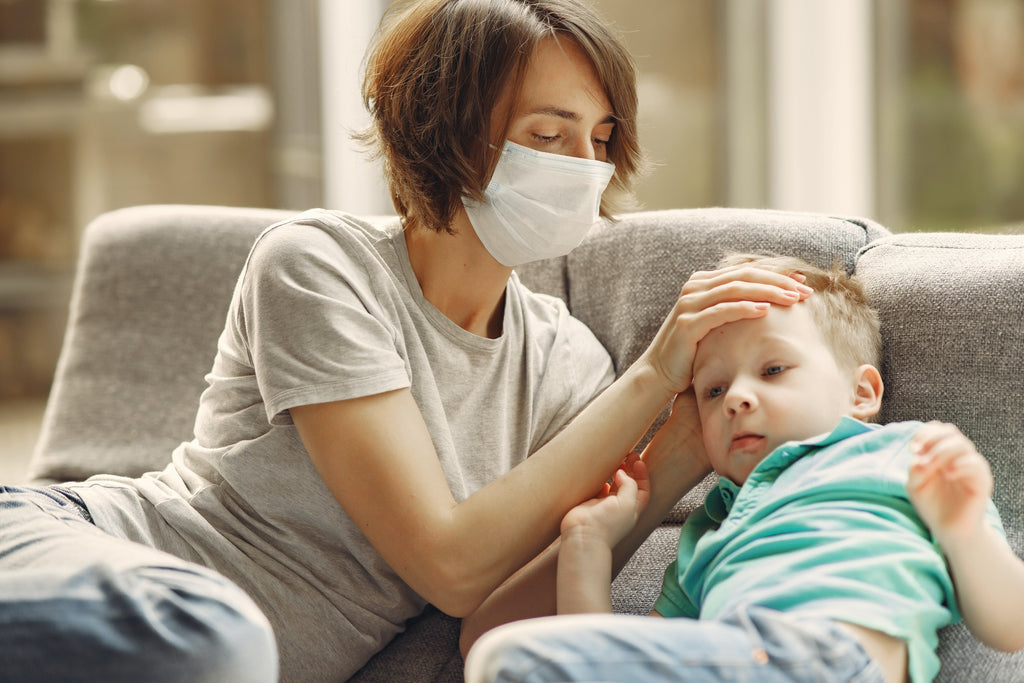 a woman wearing face mask holding her sick child