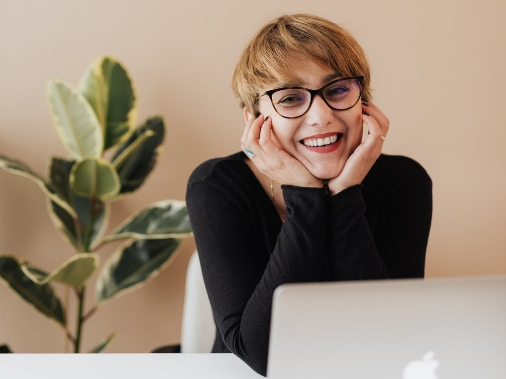 Cheerful woman smiling while sitting at table with laptop
