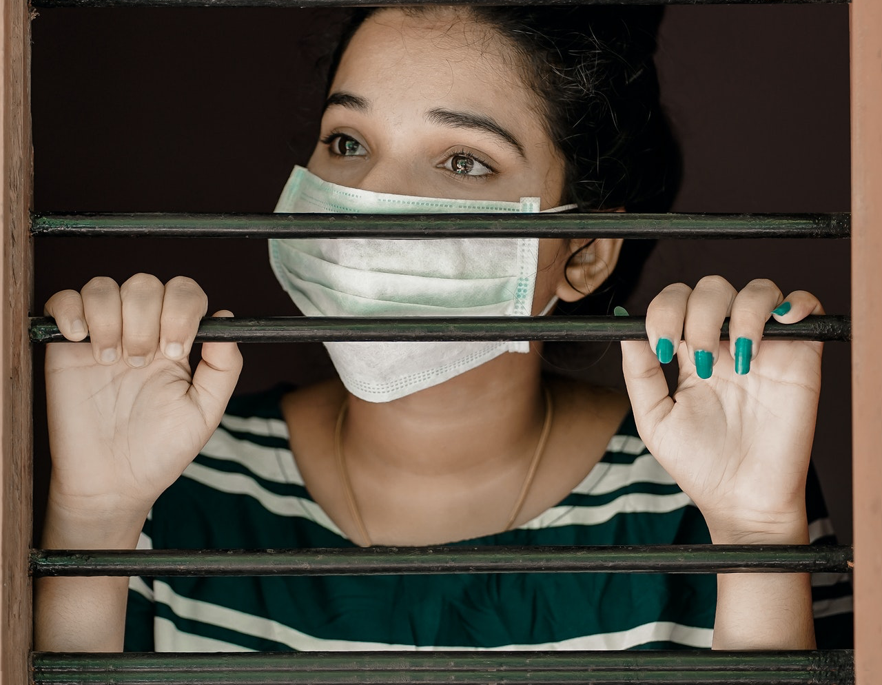 Is The COVID-19 Dilemma Over? A young woman wearing a surgical face mask behind jail bars.