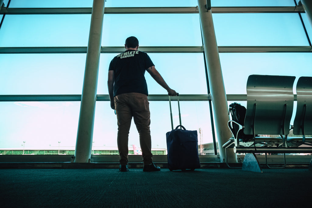 a man standing with his luggage at the airport