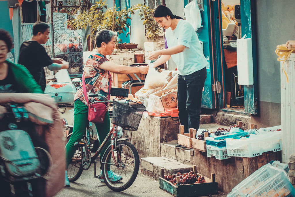 people on the street market selling and buying goods