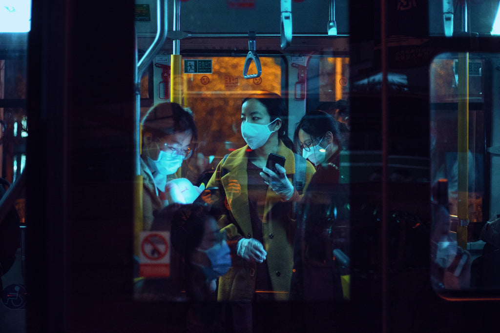 group of people on a train wearing face masks