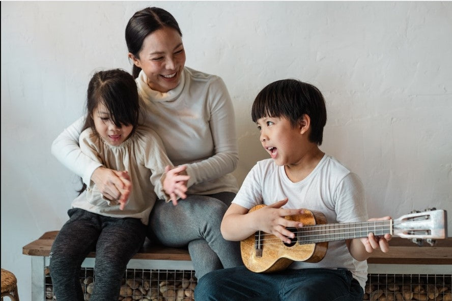 happy family singing song and a boy playing a guitar
