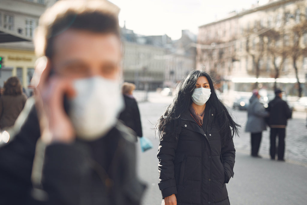 woman in black coat wearing face mask on the street
