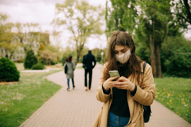 woman in brown jacket wearing a face mask and  using a smartphone