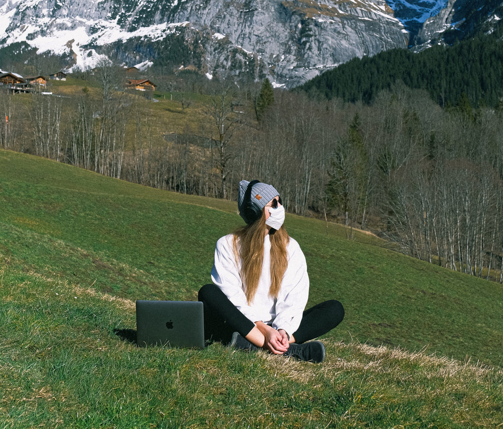 a woman wearing facemask on a mountain