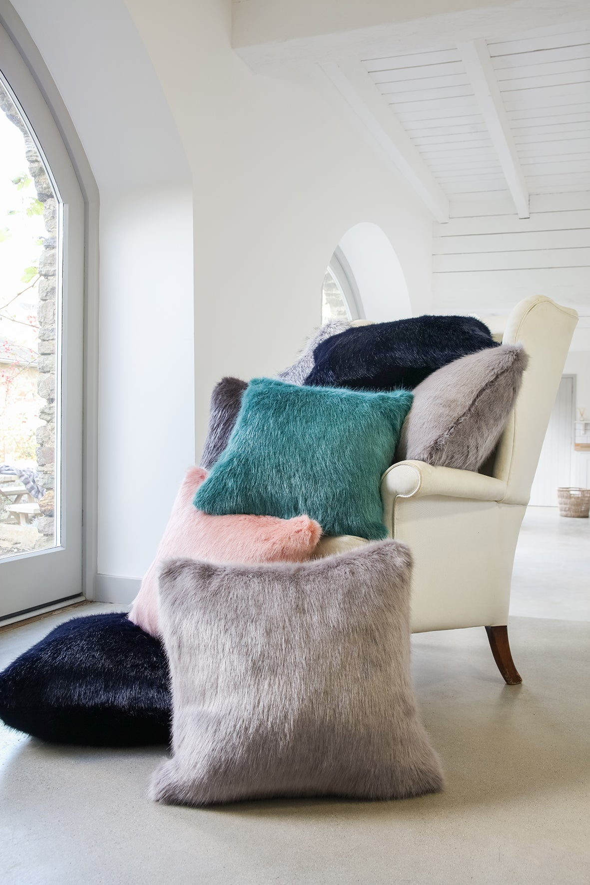 Stack of faux fur cushions on an armchair