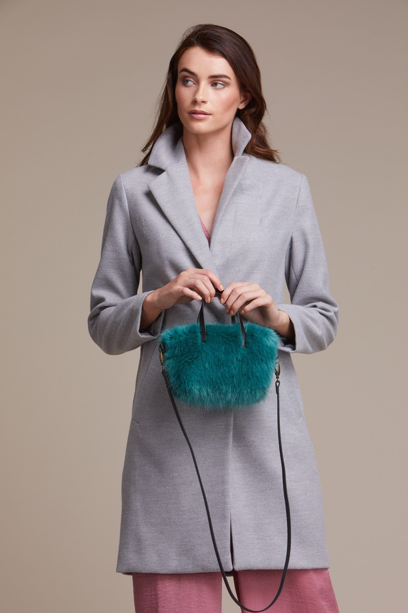 Lady holding sea green faux fur bag by Helen Moore