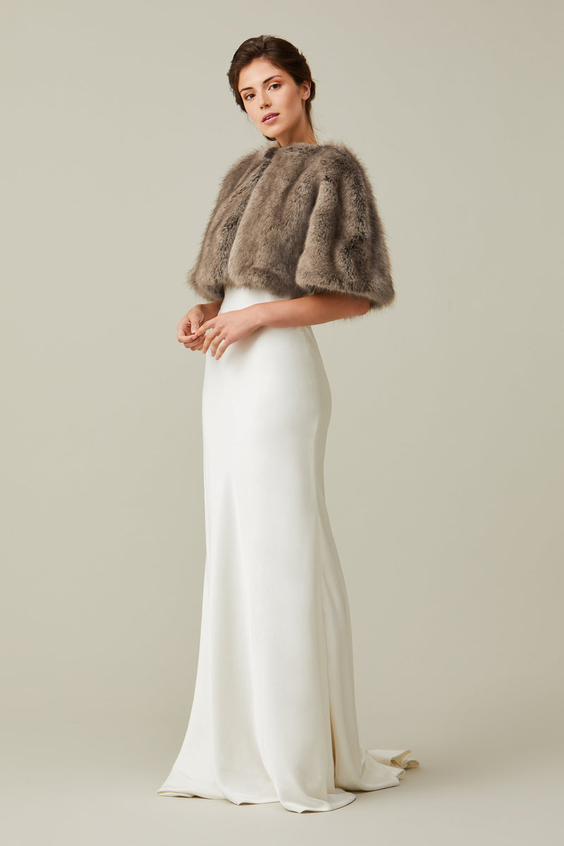 Model wears a light brown faux fur short cape by Helen Moore