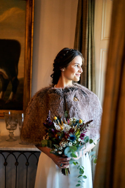 fBride standing with a bouquet wearing a light brown faux fur short cape by Helen Moore