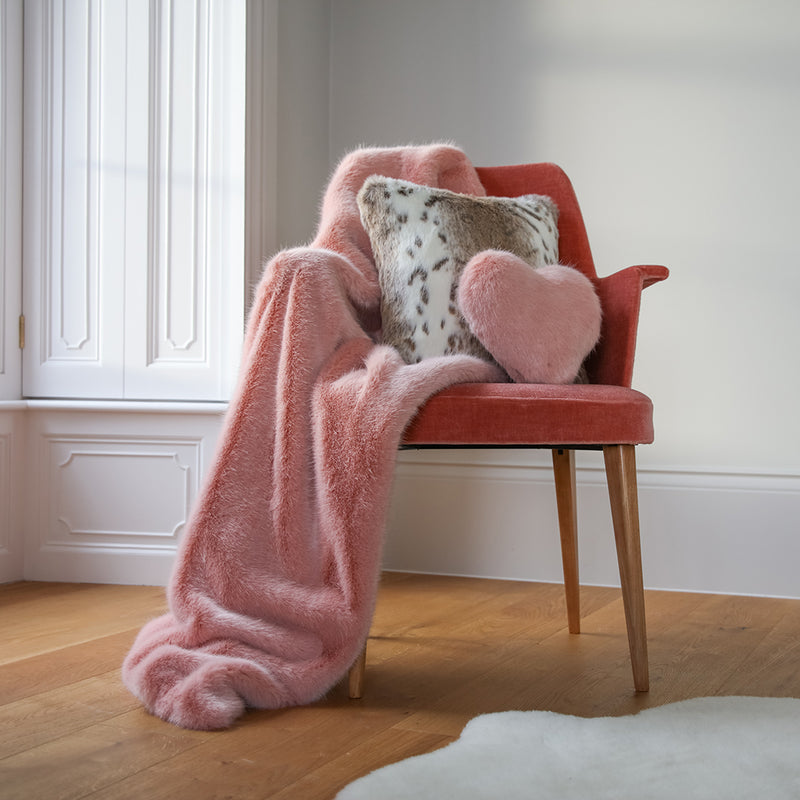 Dusky pink faux fur comforter throw by Helen Moore on a chair with faux fur cushions
