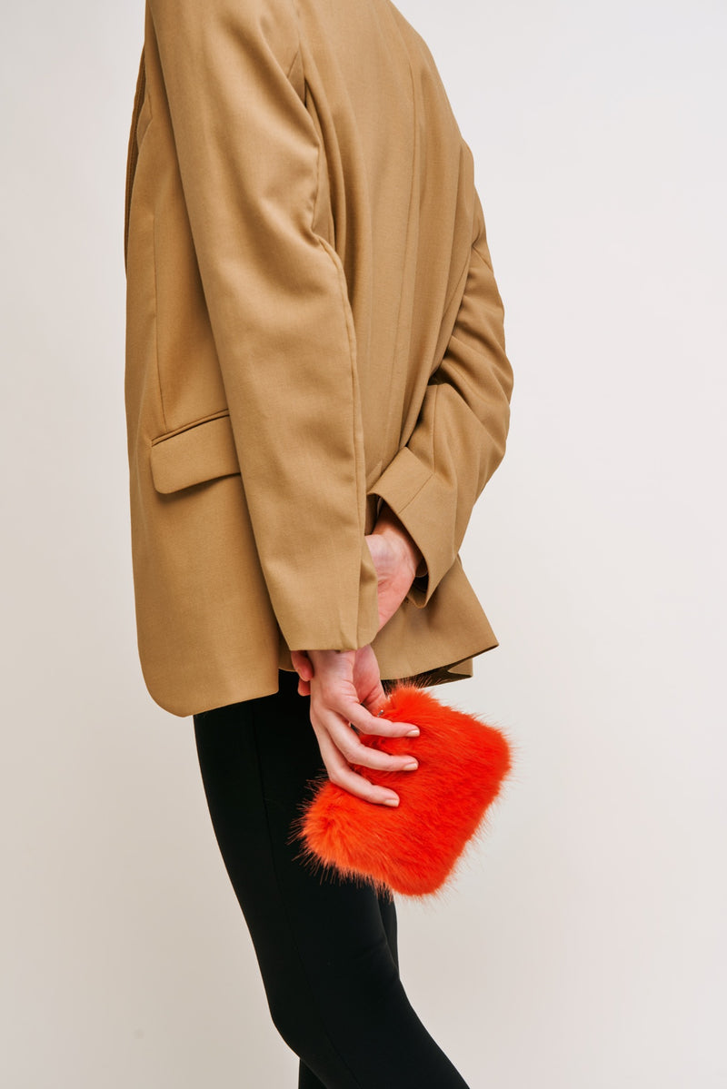 Model holding a blaze orange faux fur coin purse by Helen Moore