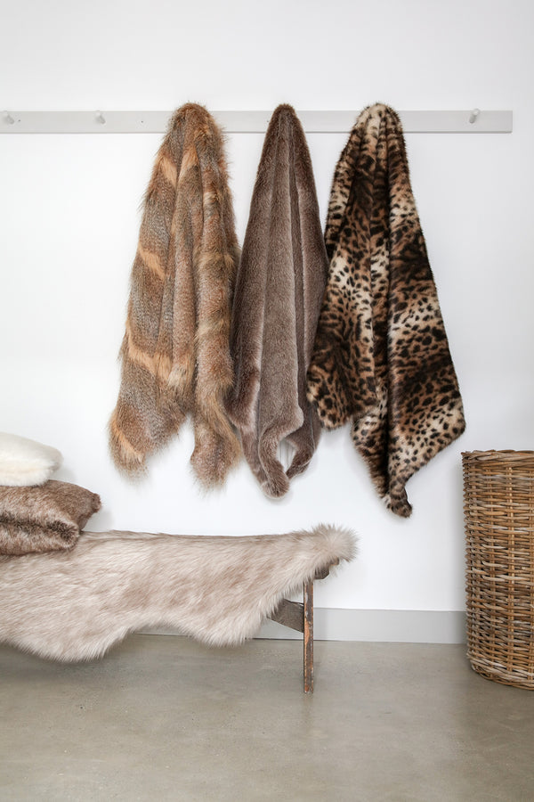 Three faux fur comforters by Helen Moore hanging on hooks in a hallway