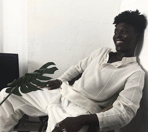Nana Kwasi Wiafe in a white outfit reclined in a chair with a branch on a white table top