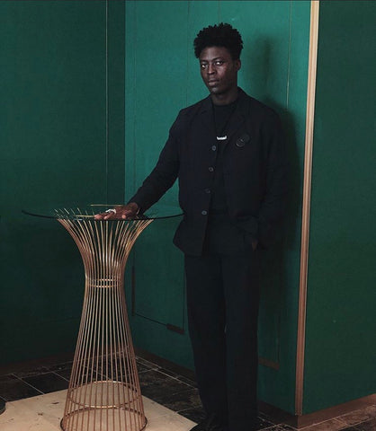 Nana Kwasi in a black outfit standing besides a gold painted cane table with his hands on the table and his other hand in his pocket. He is standing in front of a green wall