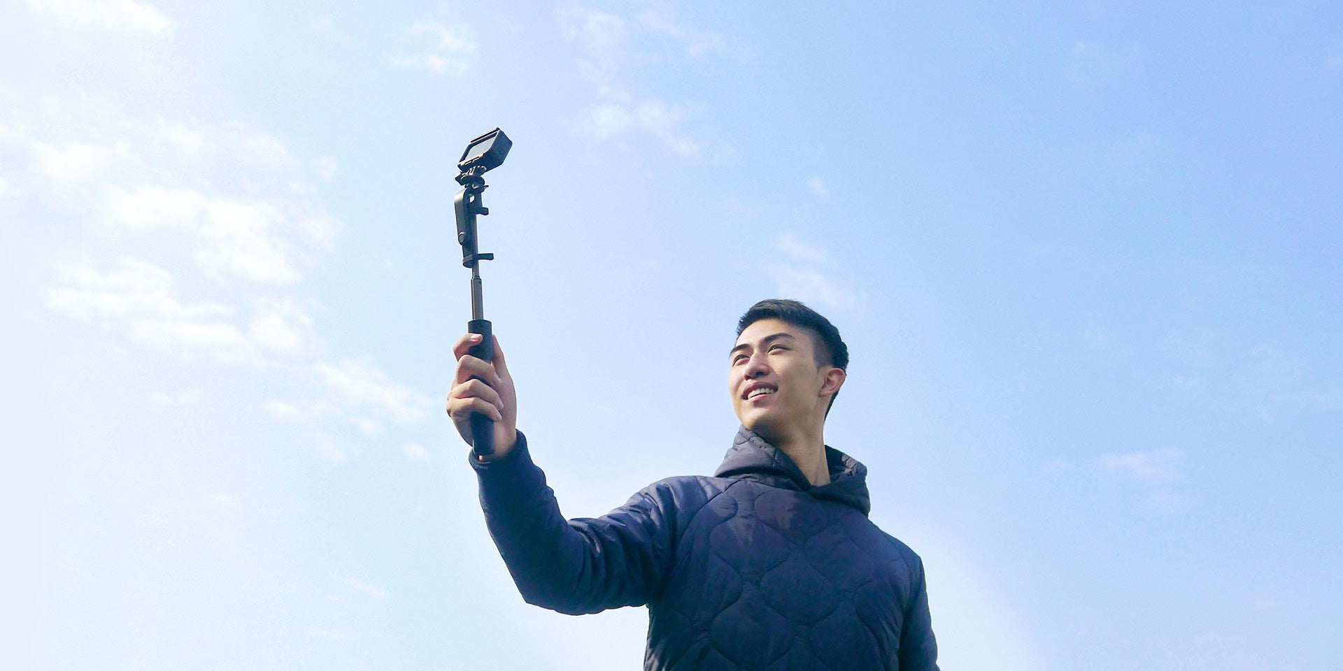 A male is taking photo with selfie stick