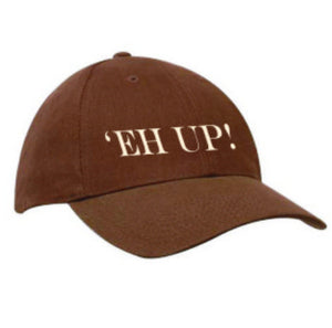 "Brown heavy cotton baseball cap, embroidered in cream thread ""Eh Up"""