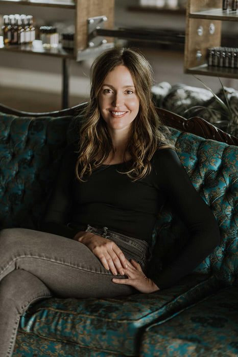 Founder Kari Asselin on dark green couch in Om Organics Apothecary