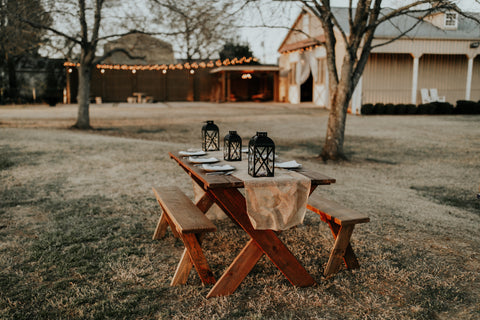 wooden picnic table outside with natural tablescape for Thanksgiving dinner