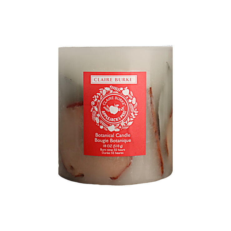 Featuring hand-arranged botanicals enveloping a center display of leafy greens, cinnamon sticks, and vibrant apple slices. The botanical candle is packed with the delightful aroma of Claire Burke's Applejack & Peel® scen