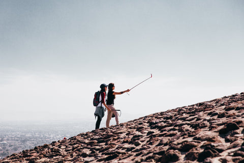 two hikers taking a photo on a mountain using a selfie stick