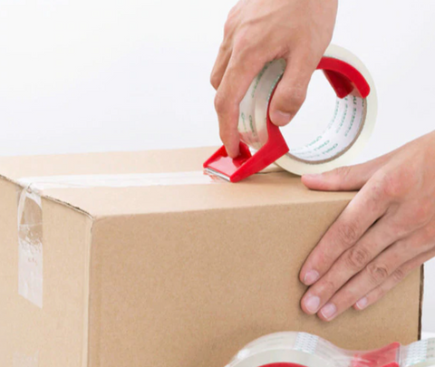 hand taping together a cardboard shipping box