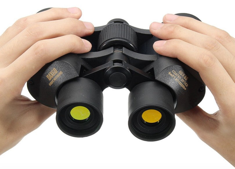 two white hands holding a pair of night vision black binoculars with yellow lens